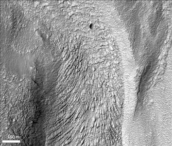 In this undated orbital photos from NASA Mars Reconnaissance Orbiter, this closeup view shows chevron texture on riverbed floor, indicating how the ice-rich material flowed fastest in the middle and was retarded along the channel walls. REUTERS/NASA/JPL/Handout
