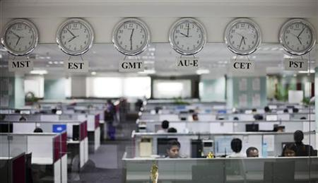 Workers are pictured beneath clocks displaying time zones in various parts of the world at an outsourcing centre in Bangalore February 29, 2012. REUTERS/Vivek Prakash