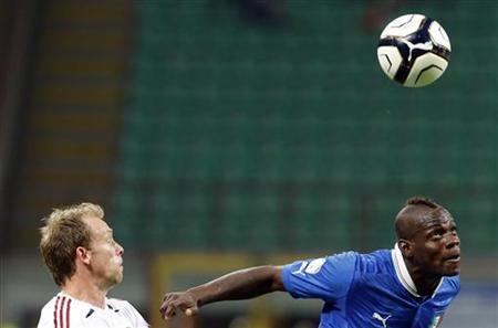 Italy's Mario Balotelli (R) challenges Michael Krohn-Dehli of Denmark during their 2014 World Cup qualifying soccer match at San Siro stadium in Milan October 16, 2012. REUTERS/Stefano Rellandini