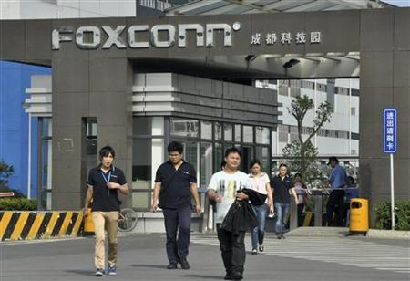 Workers walk out of the entrance to a Foxconn factory in Chengdu, Sichuan province July 4, 2012. REUTERS/Stringer/Files