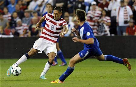 Clint Dempsey of the U.S. (L) passes against Guatemala's Elias Vasquez during the second half of the U.S. win in their 2014 World Cup qualifying soccer match in Kansas City, Kansas October 16, 2012. REUTERS/Dave Kaup