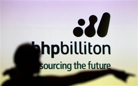 A woman gestures in front of a BHP Billiton sign during a half-year results briefing by the company's Chief Executive Marius Kloppers, in central Sydney in this February 16, 2011 file photograph. REUTERS/Tim Wimborne/Files