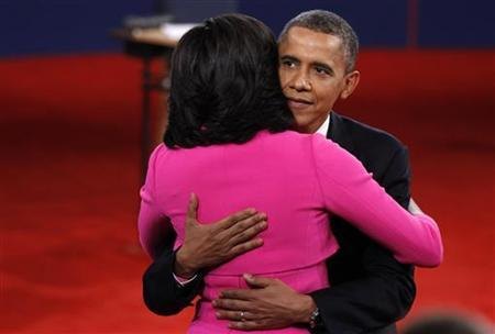 U.S. President Barack Obama embraces first lady Michelle Obama after the conclusion of the second U.S. presidential debate in Hempstead, New York, October 16, 2012. REUTERS/Jim Young