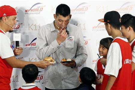 NBA basketball player Jeremy Lin (C) of the Houston Rockets eats sushi during a promotional event in Hong Kong August 24, 2012. REUTERS/Tyrone Siu