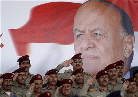 Military officers salute in front of poster of Yemen's President Abd-Rabbu Mansour Hadi during a military parade celebrating the 50th anniversary of North Yemen's revolution in Sanaa September 26, 2012. REUTERS/Khaled Abdullah