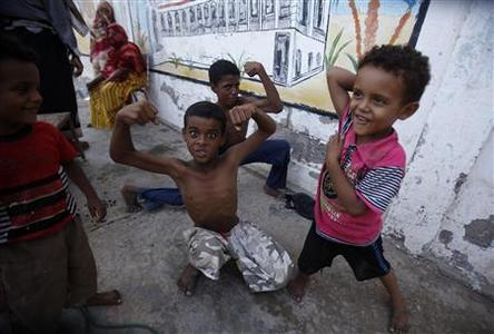 Children show their muscles at a school sheltering them in the southern Yemeni port city of Aden October 8, 2012. Yemenis who fled the fighting after al Qaeda militants occupied their home towns are now under pressure to go home, but many are hesitating for fear of the group's lingering influence despite assurances that the area east of Aden is now safe. Around 150,000 people left Jaar and Zinjibar after militants calling themselves the Ansar al-Sharia swept in between March and May 2011, taking advantage of a security vacuum during an uprising against then-President Ali Abdullah Saleh. Picture taken October 8, 2012. To match Feature YEMEN-QAEDA/DISPLACED REUTERS/Khaled Abdullah