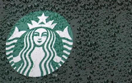 Raindrops are seen on the Starbucks logo on a signage at a branch of the coffee shop chain in London October 8, 2012. REUTERS/Luke Macgregor