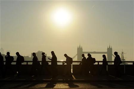 Workers cross London Bridge, with Tower Bridge seen behind, during the morning rush hour in London September 30, 2011. REUTERS/Paul Hackett