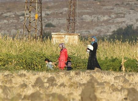Syrians walk on the Turkish-Syrian border near the town of Reyhali in Hatay province October 17, 2012. REUTERS/Osman Orsal