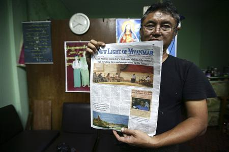 Editor-in-chief Than Myint Tun holds up a dummy of the New Light of Myanmar, due to be released in colour for the first time in October 2012, at its offices outside Naypyitaw September 19, 2012. REUTERS/Minzayar