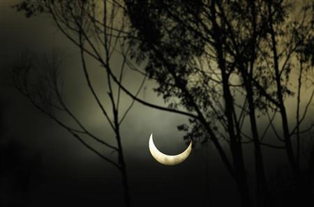 The moon passes between the sun and the earth as viewed through coastal fog rolling in from the ocean in Encinitas, California May 20, 2012. REUTERS/Mike Blake
