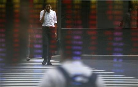 A man using a mobile phone is reflected on an electronic monitor displaying share prices at a brokerage in Tokyo September 7, 2012. REUTERS/Issei Kato/Files