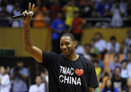 Former NBA basketball player Tracy McGrady of Detroit Pistons gestures to his fans at a stadium during a promotional event of his China tour in Hefei, Anhui province August 27, 2011. Picture taken August 27, 2011. REUTERS/Stringer