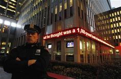 Офицер полиции Нью-Йорка стоит около бегущей новостной строки с сообщением о задержании гражданина Бангладеш, 17 октября 2012 года. ФБР задержало в среду молодого человека по обвинению в попытке взорвать здание Федерального резервного банка в Нью-Йорке при помощи устройства, которое, как он полагал, было 450-килограммовой бомбой, сообщили федеральные власти. REUTERS/Lucas Jackson