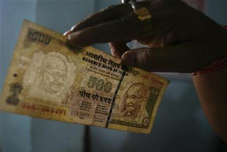 An employee checks a 500 Indian rupee note at a cash counter inside a bank in Agartala August 9, 2011. REUTERS/Jayanta Dey/Files