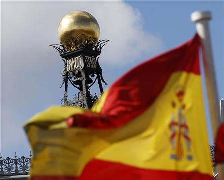 A Spanish flag flutters in the wind in front of the dome of Bank of Spain headquarters in central Madrid September 24, 2012. REUTERS/Sergio Perez