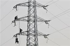 Labourers inspect and repair an electricity pylon in Yingtan, Jiangxi province December 21, 2010. REUTERS/Stringer