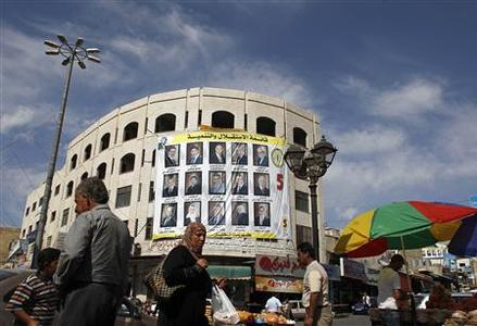 Palestinians walk past a a municipal election banner in the West Bank city of Hebron October 17, 2012. Palestinians in the West Bank go to the polls on Saturday in long-delayed municipal elections that have exacerbated deep divisions in the occupied territory and stoked scepticism about the senior leadership. REUTERS/Ammar Awad