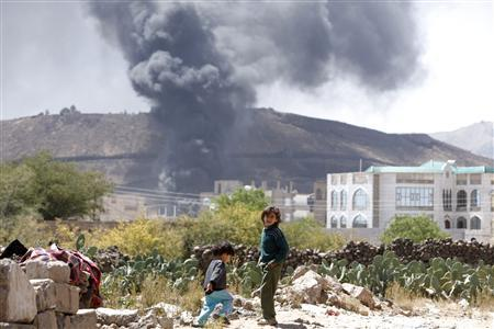Children stand near their house as smoke rises after explosions were set off at the army's First Armoured Division headquarters in Sanaa October 18, 2012. A shell fired near a Yemeni general's military headquarters in the capital Sanaa hit a weapons depot and set off a series of explosions on Thursday, a Yemeni army source said. REUTERS/Khaled Abdullah