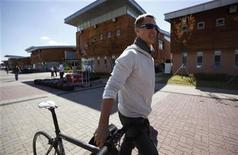 Mercedes Formula One driver Michael Schumacher of Germany pushes a bicycle as he arrives ahead of the South Korean F1 Grand Prix at the Korea International Circuit in Yeongam October 11, 2012. REUTERS/Woohae Cho