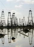 Буровые вышки на нефтяном месторождении на побережье Каспийского моря возле Баку, 6 октября 2005 года. Туркмения оценивает иностранные инвестиции в освоение национального сектора Каспия в рамках соглашений о разделе продукции (СРП) в 2012 году в $3,8 миллиарда, сказал заместитель председателя Госагенства по углевородным ресурсам Ашир Беглиев. REUTERS/Grigory Dukor