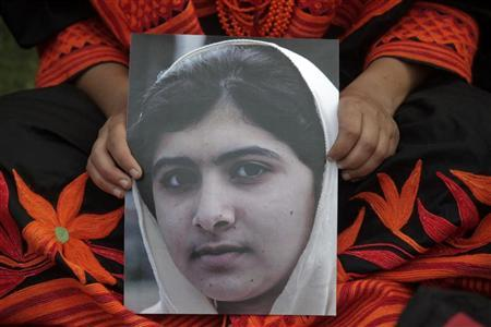 A student holds an image of Malala Yousufzai, who was shot on Tuesday by the Taliban, during a rally in Lahore October 14, 2012. REUTERS/Mohsin Raza