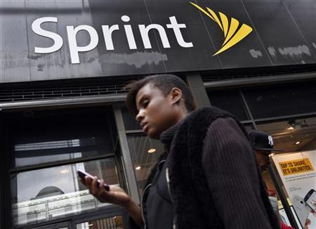 A woman uses her phone as she walks past a Sprint store in New York's financial district, October 15, 2012. REUTERS/Brendan McDermid