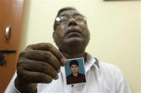 Quazi Mohammad Ahsanullah, father of Quazi Mohammad Rezwanul Ahsan Nafis, holds a photograph of his son inside his residence at Uttar Jatrabari in Dhaka October 18, 2012. REUTERS/Andrew Biraj