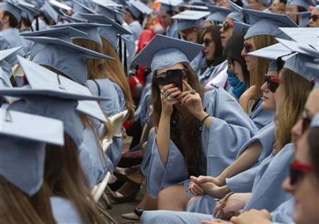 A graduate from Columbia University's Barnard College uses her a mobile phone to take a photo during the university's commencement ceremony in New York May 16, 2012. REUTERS/Keith Bedford