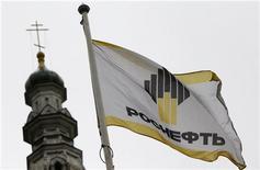 Флаг с логотипом Роснефти возле офиса компании в Москве, 18 октября 2012 года. Госкомпания Роснефть не будет претендовать на поглощение всей российско-британской ТНК-BP, довольствуясь долей в размере 50 процентов, сказал Рейтер министр энергетики Александр Новак в кулуарах нефтяной конференции газеты Ведомости. REUTERS/Maxim Shemetov
