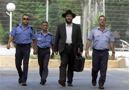 Former Israeli government kingmaker and ex-leader of the ultra-orthodox Shas Party Aryeh Deri is escorted by policemen as he walks out of prison July 15, 2002 after serving two years of a three-years sentence for corruption. Deri, released a year early for ''good behaviour'', said he would devote himself to social work and that he would seek a retrial. REUTERS/Nir Elias NIR/RS