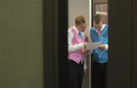 Dale Frost (L) and Mark Massey read their wedding certificate at the City Clerk's Office in New York October 11, 2012. REUTERS/Andrew Kelly