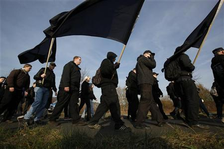 Neo-Nazis walk with black flags through the town of Remagen, some 25 km (15 miles) south of Bonn November 19, 2011. REUTERS/Wolfgang Rattay