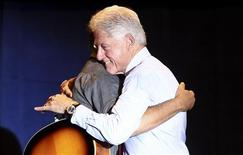 Rocker Bruce Springsteen (L) gets a hug from former U.S. President Bill Clinton at a concert rally at Cuyahoga Community College to re-elect U.S. President Barack Obama in Parma, Ohio October 18, 2012. REUTERS/Aaron Josefczyk