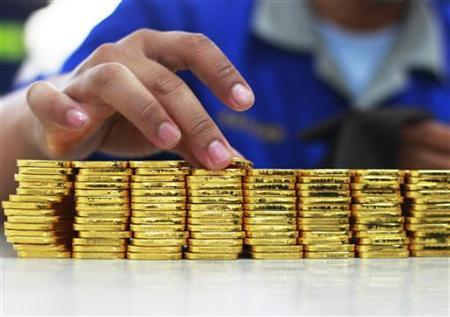An employee holds a gold piece, each weighing 100 grams, at the state-owned mining company PT Antam Tbk metal refinery in Jakarta July 13, 2012. Picture taken July 13, 2012. REUTERS/Beawiharta