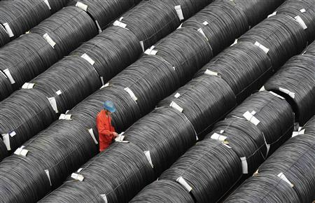 A worker checks on coils of steel at a factory in Dalian, Liaoning province October 18, 2012. REUTERS/China Daily