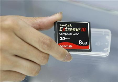 An employee of a computer shop poses with a SanDisk compact flash memory card inside a computer mall in Taipei September 17, 2008. REUTERS/Nicky Loh