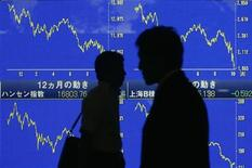 Силуэты прохожих на фоне экранов с динамикой японских индексов в Токио, 7 октября 2008 года. Глобальные инвесторы временно охладели к фондам, ориентированным на РФ, в то время как остальные представители развивающихся рынков получают новые порции свежей ликвидности, следует из отчета EPFR Global, на который ссылаются Уралсиб Капитал и Альфа-банк. REUTERS/Yuriko Nakao