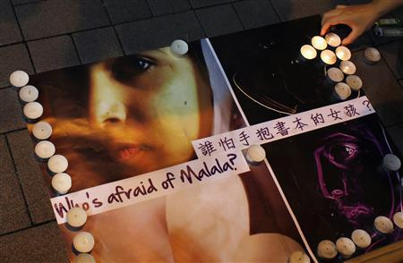 A portrait of 14-year-old Pakistani girl, Malala Yousufzai, is displayed during a candlelight vigil by a women's group in Hong Kong October 19, 2012. Yousufzai, who was shot in the head by Taliban gunmen, is 'not out of the woods' but is doing well and has been able to stand for the first time with some help, doctors at the British hospital treating her said on Friday. Yousufzai was flown from Pakistan to Birmingham to receive treatment after the attack earlier this month, which drew widespread international condemnation. REUTERS-Bobby Yip