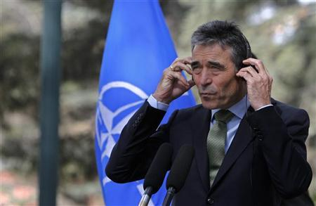 NATO Secretary General Anders Fogh Rasmussen adjusts his headphones as he listens to a question during a joint news conference with Afghan President Hamid Karzai in Kabul October 18, 2012. REUTERS/Omar Sobhani