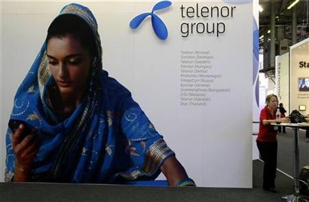 A visitor rests under a Telenor Group sign at the GSMA Mobile World Conference in Barcelona February 18, 2009. REUTERS/Gustau Nacarino/Files