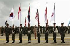 "Thai soldiers carry national flags as they participate in the opening ceremony of the annual joint ""Cobra Gold 2010"" (CG10) military exercise at U-tapao airport in Rayong province in this February 1, 2010 file photo. The United States will invite Myanmar to the world's largest multinational military field exercise, a powerful symbolic gesture toward a military with a grim human rights record and a milestone in its rapprochement with the West. Myanmar will be allowed to observe Cobra Gold, which brings together more than 10,000 American and Thai military personnel and participants from other Asian countries for joint annual manoeuvres, officials from countries participating in the exercises told Reuters. REUTERS/Chaiwat Subprasom/Files"