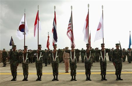 Thai soldiers carry national flags as they participate in the opening ceremony of the annual joint ''Cobra Gold 2010'' (CG10) military exercise at U-tapao airport in Rayong province in this February 1, 2010 file photo. The United States will invite Myanmar to the world's largest multinational military field exercise, a powerful symbolic gesture toward a military with a grim human rights record and a milestone in its rapprochement with the West. Myanmar will be allowed to observe Cobra Gold, which brings together more than 10,000 American and Thai military personnel and participants from other Asian countries for joint annual manoeuvres, officials from countries participating in the exercises told Reuters. REUTERS/Chaiwat Subprasom/Files