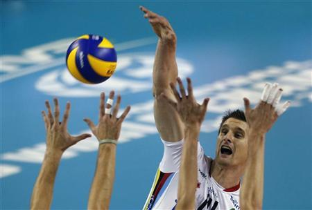 Italy's Trentino Diatec Jan Stokr (14) spikes the ball against Matthew Anderson (L) and Alexander Obrosimov of Russia's Zenit Kazan during their FIVB Men's semi-final Volleyball Clubs World Championship match in Doha, October 18, 2012. REUTERS/Fadi Al-Assaad