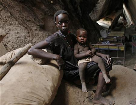 A woman holds her child in a cave in Bram village in the Nuba Mountains, South Kordofan, April 28, 2012. REUTERS/Goran Tomasevic
