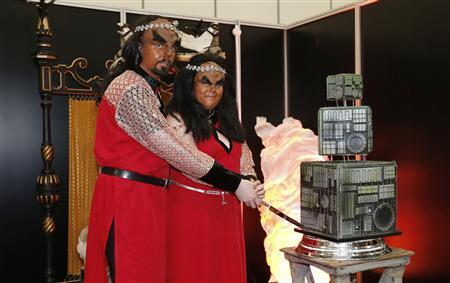 Sonnie Gustavsson (L) and Jossie Sockertopp from Sweden pose with their wedding cake after getting married in a Klingon wedding ceremony at the ''Destination Star Trek London'' convention in London October 19, 2012. REUTERS/Suzanne Plunkett