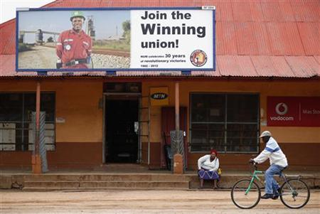 A woman sits beneath a recruitment poster for the National Union of mineworkers close to the the entrance of the Royal Bafokeng Platinum Rasimone mine near Phokeng in the North West province October 13, 2012. REUTERS/Mike Hutchings