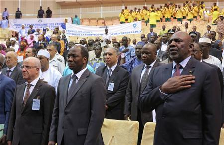 (front R -L) Mali's Prime Minister Cheick Modibo Diarra, Burkina Faso's Minister of Foreign Affairs Djibril Bassole and Algeria's Foreign Minister Mourad Medelci stand at attention for the national anthem before the start of a high level international meeting in Bamako, October 19, 2012. REUTERS/Adama Diarra
