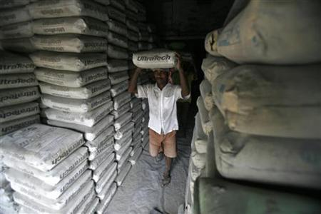 A labourer carries a sack of Ultratech cement inside a shop in Agartala June 22, 2012. REUTERS/Jayanta Dey/Files