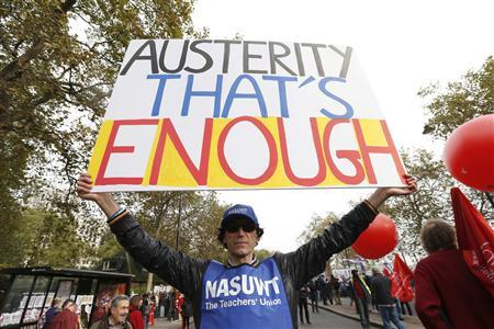 A demonstrator holds a placard before the start of a protest, on the Embankment, in central London October 20, 2012. REUTERS/Suzanne Plunkett